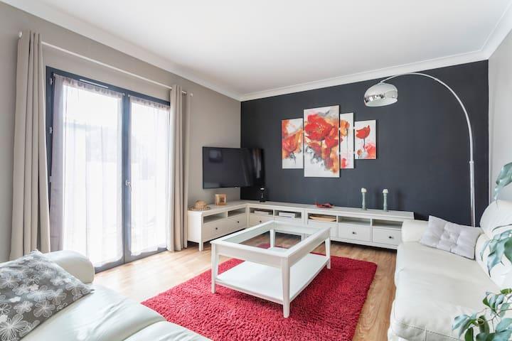 L'espace salon et salle à manger Le Bel Appartement dispose d'un salon lumineux et confortable avec ses deux canapés, sa table basse et une télévision écran plat.