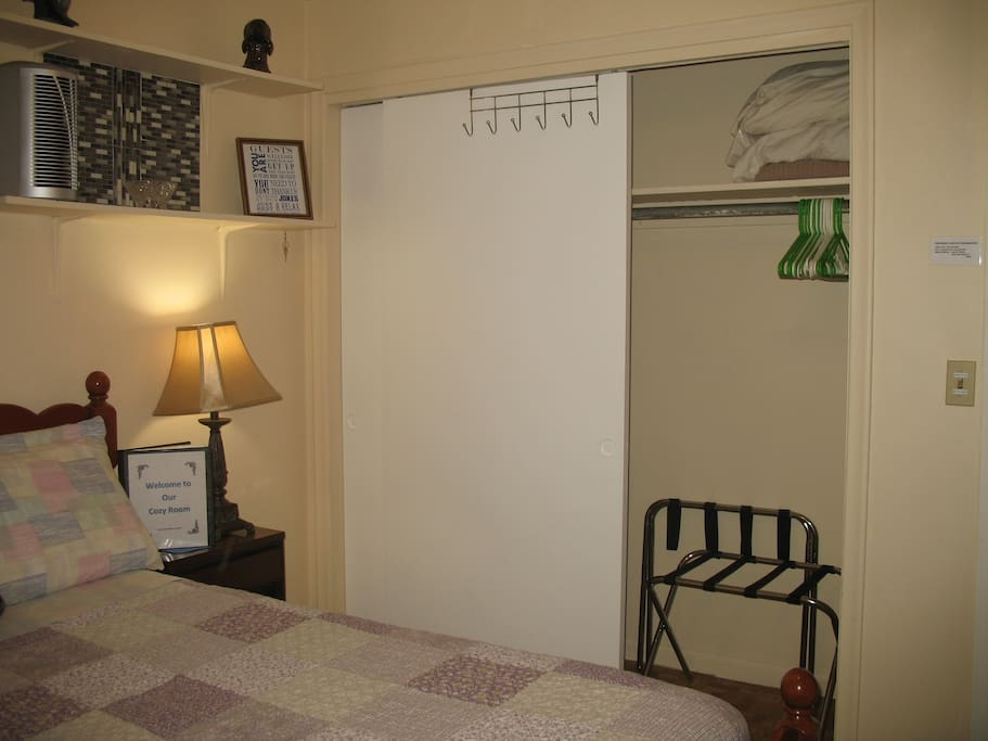 Closet with luggage racks and hangers.