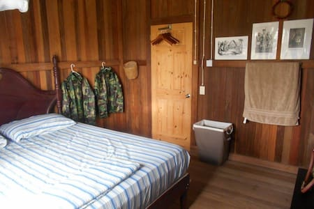 Your private room with King Sized bed with 2 pillows, visible are towels, rain-suits & boots, laundry basket (as your clothes will be hand washed for you), small refuse basket, mosquito net,