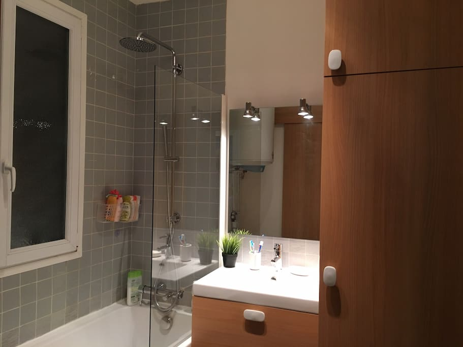 Salle de bain avec baignoire, lave-linge et sèche-linge