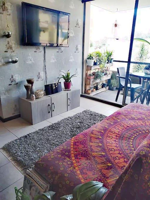 Sala con con TV compartida y balcón.