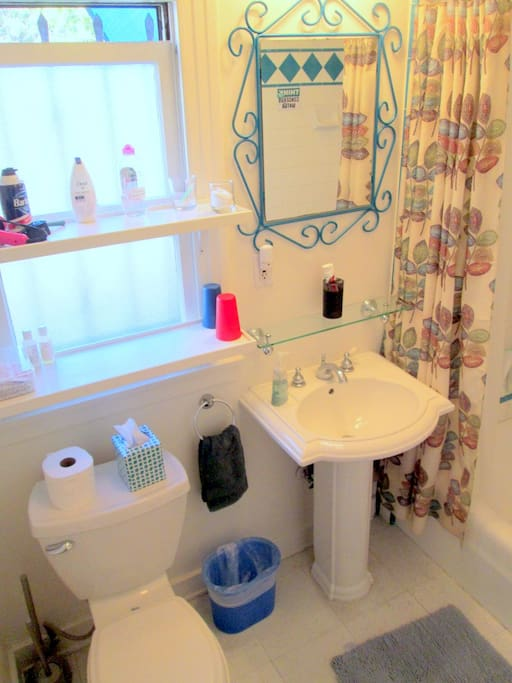 Full bathroom, with tub, shower, sink and toilet--and shelves for your toiletries.