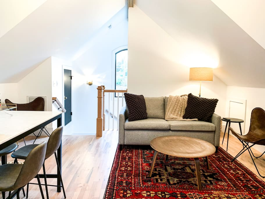Our living + kitchen features a Room + Board couch with a Queen foam mattress, ample seating and lighting, cozy throws and rugs, and a marble-topped bar area.