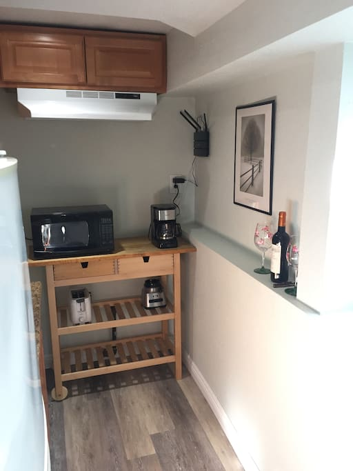 Kitchenette with coffee maker, toaster, microwave, blender, sink and fridge.