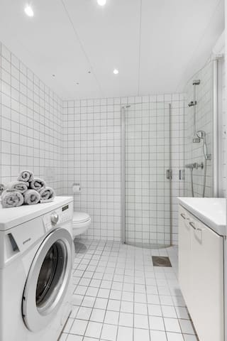 Bathroom with shower, toilet and washing machine.