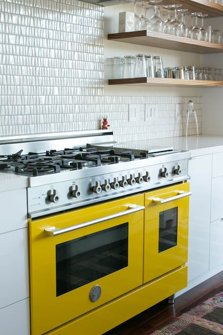 Foodies will love cooking on the yellow Bertazzoni range with 6 burners, griddle, and two ovens.
