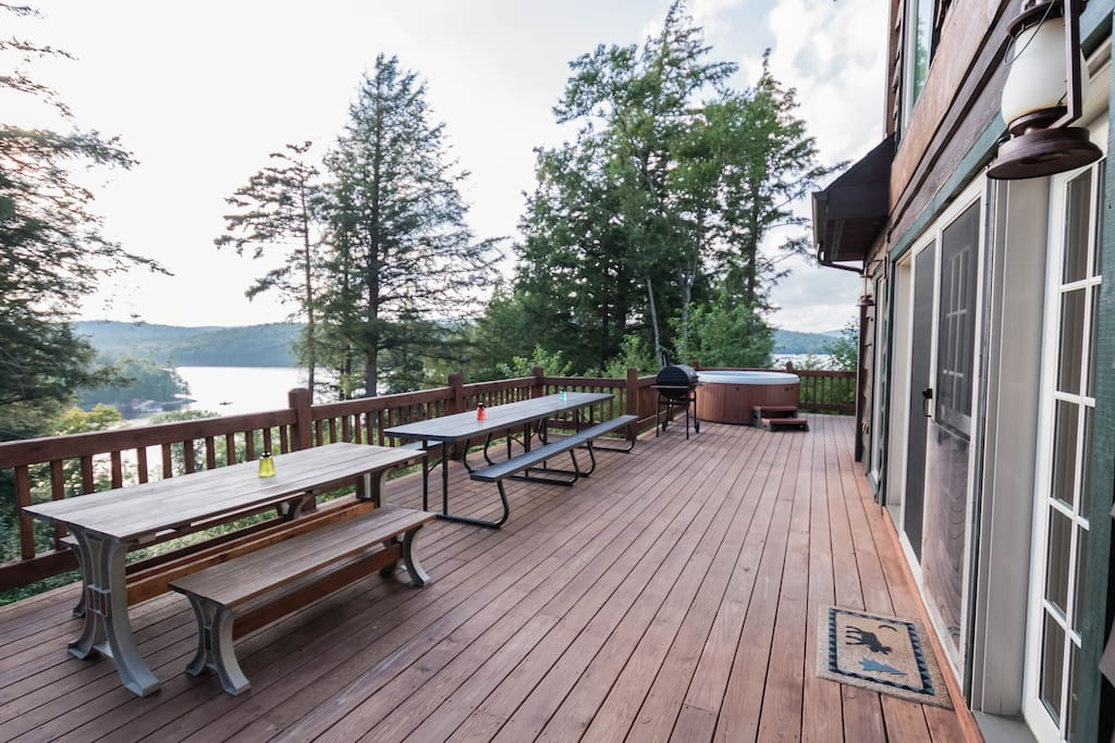 Deck overlooking Tupper Lake with hot tub and charcoal grill, seats 22