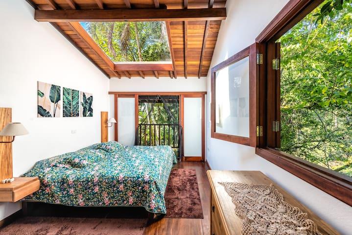 Vista da porta do banheiro para o dormitório e varanda. Em cima da cama tem uma claraboia que da para fechar via interruptor na parede atras da cama king.