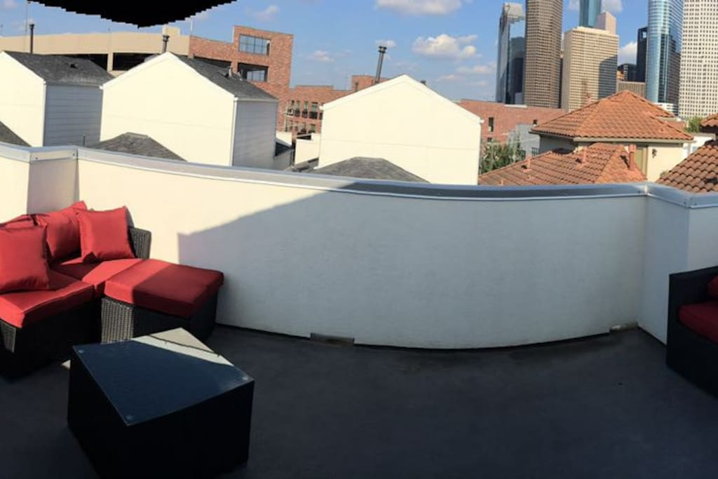 Relax and unwind with full rooftop furniture to view downtown buildings