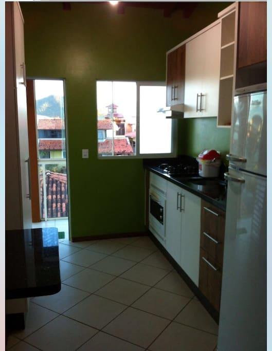 Cozinha toda com armários e com utensílios domésticos com microondas, fogão, geladeira.