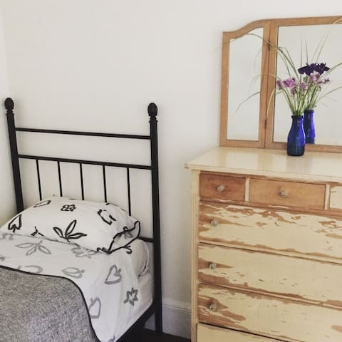 Bedroom 1, with single bed and chest of drawers. Bedroom also has an easy chair and bookshelf.