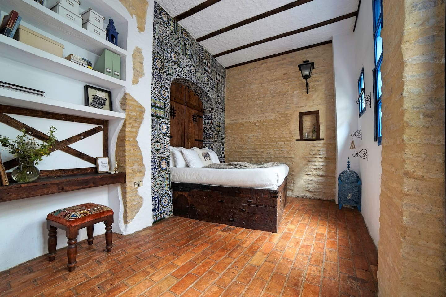 "The first view when you enter. The arch is lined with very old recycled tiles I found when restoring the house. The big wooden door that functions as a ""headboard"" is hand made from raw heavy would and built by me. Jump on the bed its very soft."