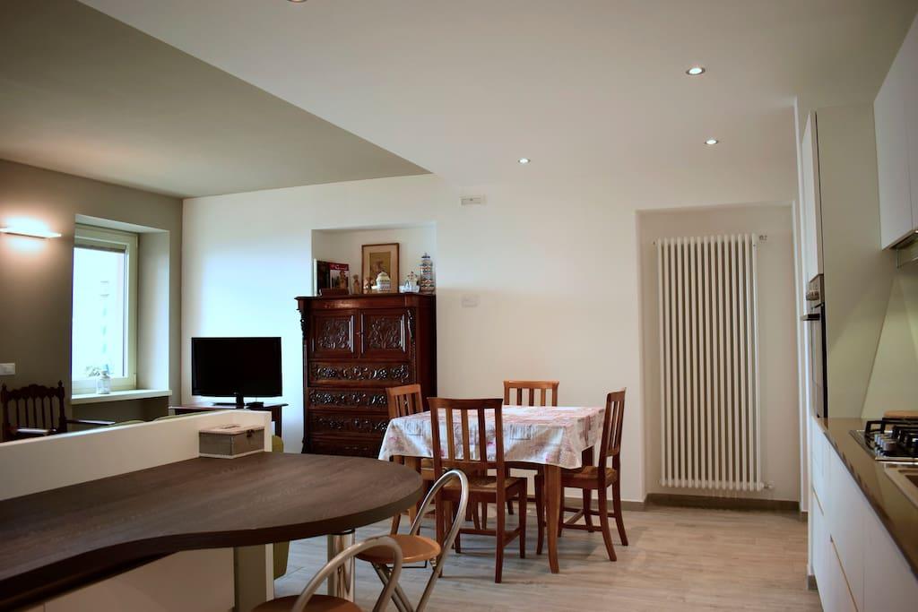 Cucina e soggiorno con due divani , tavolo da pranzo e affaccio al balcone vista lago