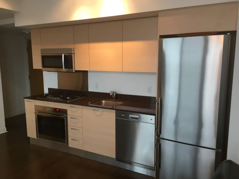 Clean Kitchen With All Stainless Steel Appliances Ready For Guests.