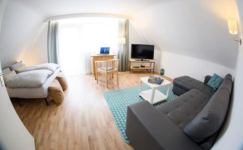 Schlafzimmer 1 mit bequemen Sofa ,einen Schreibtisch und Balkon