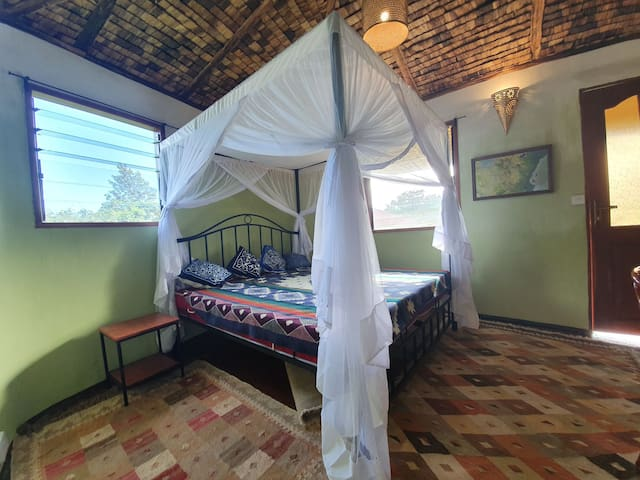 The bedroom has a comfortable queen size bed, cozy wooden floors and traditional banana leave ceilings.
