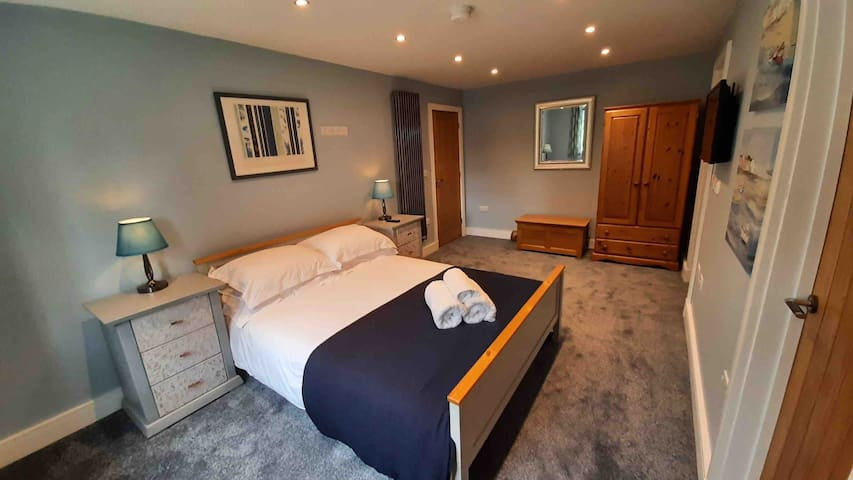 Master bedroom with king size bed, plenty of space of a cot if required, wardrobe with hanging space and drawers, plenty of space for suitcases, to inch lamps with usb chargers, bedroom seating, curtains and blackout blind.
