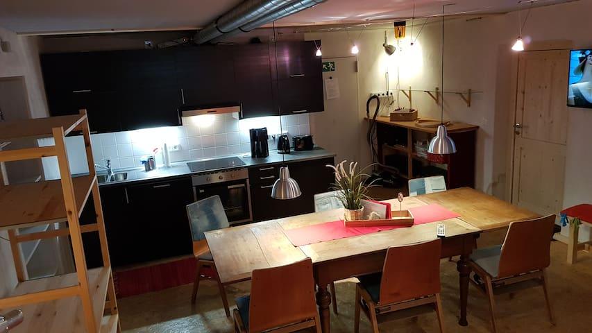 Küchenzeile in der Wohnküche, mittig hinten die Wohnungstür.