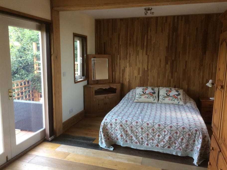 Separate bedroom with French doors leading onto sun deck and garden
