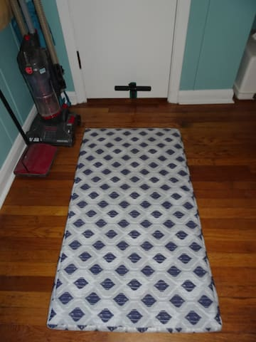 sit-up bar attached to a back-room closet door, with a mat on the floor should you wish to do sit-ups