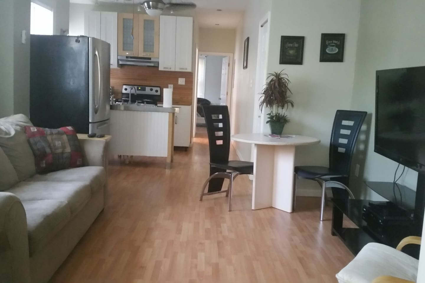 """A livingroom with a comfy couch, a small eating table and 46"""" Flat Screen"""