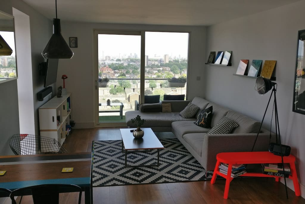 Open-plan living room with sofa, dining table and kitchen, backing onto the balcony with views over East London.