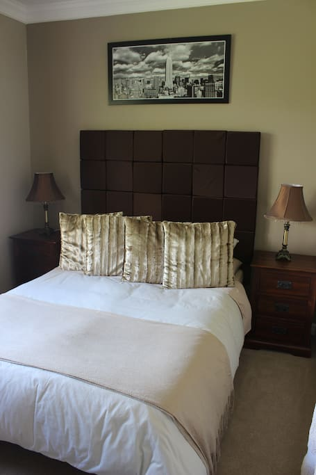 Comfortable second bedroom with dresser and wardrobe