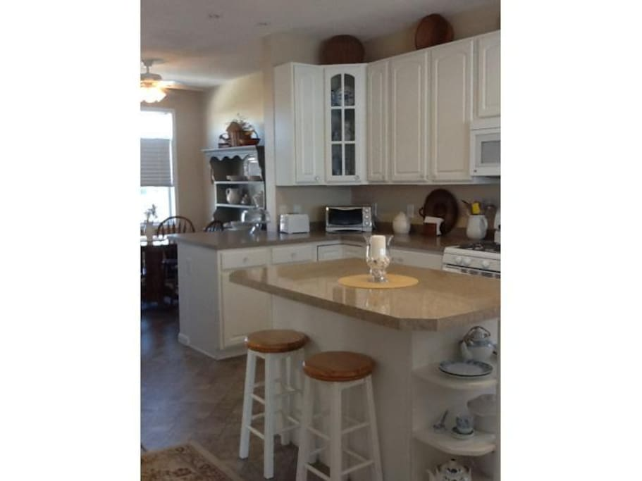 Kitchen with 3 breakfast nooks and a dining table for four with decks in front & in back of house