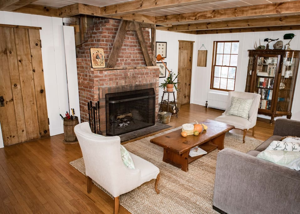 LIVING AREA (1st Floor): We renovated the old stained paneling to showcase the original rustic raw wood beams and doors. The white wood paneling and hardwood floors brought some modernity to this old room without deviating from the home's original soul.