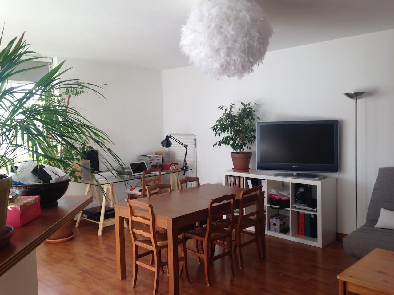 Grand salon avec table à manger et espace bureau.