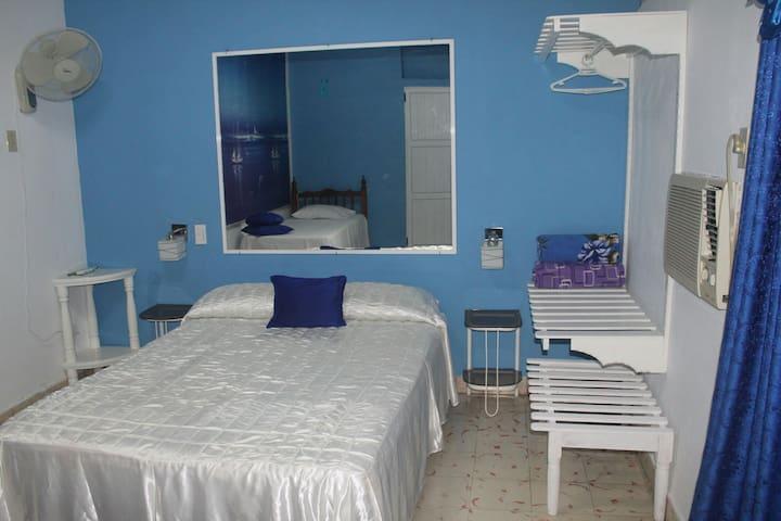 Amplia habitación,  con acceso a la terraza, dos camas y baño privado en la habitación.