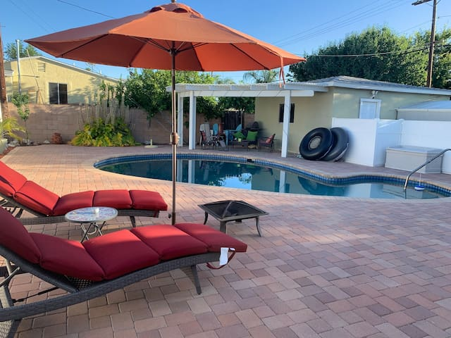 Pool area with additional seating, pool floaters, fire pit and pool-side grill