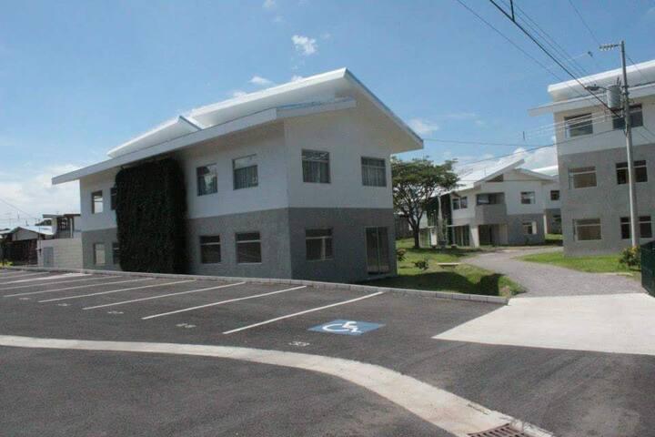 Parqueo del Condo. La casa del fondo en 2do piso es la disponible. Condo parking lot. House in background at 2nd floor is the one available.