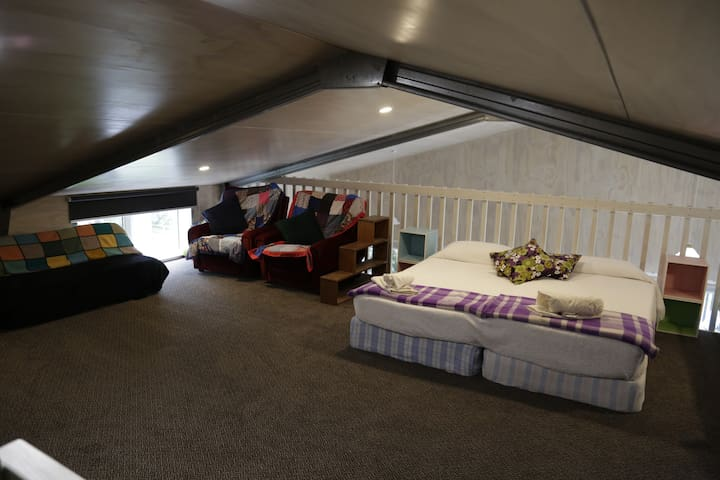 small lounge with foldout and 2 singles often pushed together. More Mattresses stacked in the corner