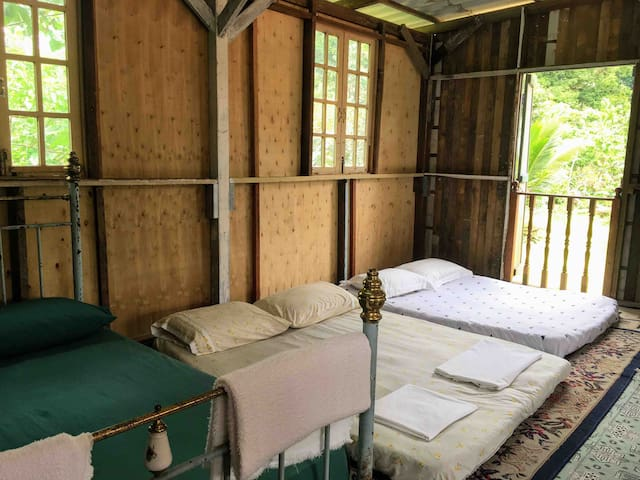 Bedroom 2: A rustic look spacious and big family room upstair with nice front view; with one standing and a wall fan; the long wooden window overlooking the lovely garden, the gazebo and the river.