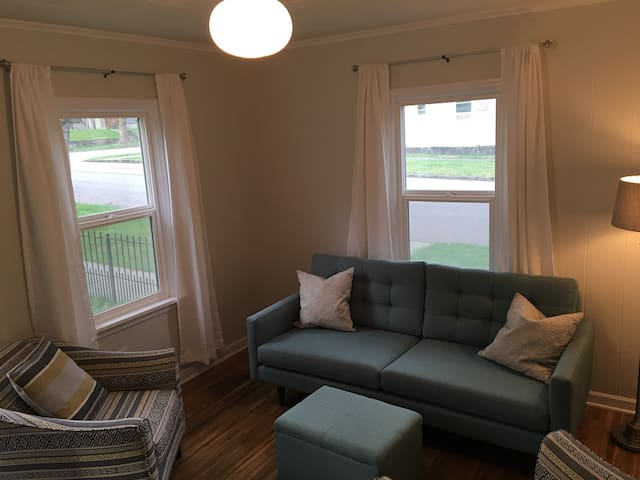 Front door enters into the living room with couch and comfortable sitting chairs.