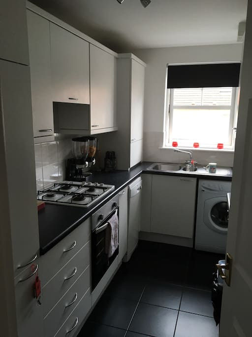Fitted kitchen with oven, grill, dishwasher, washing machine and microwave.