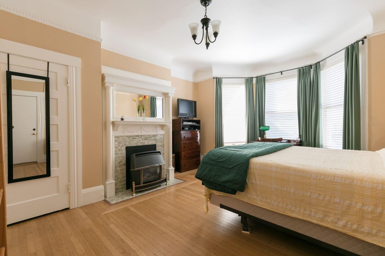 Main room showing closet door original Edwardian fireplace with gas fire heater, dresser with entertainment center