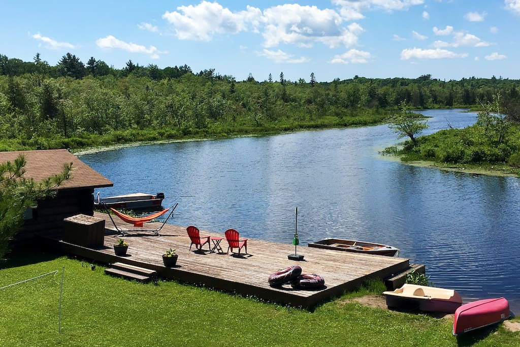 Boathouse and dock with a hammock, water toys, rowboat, pedal boat and canoe.