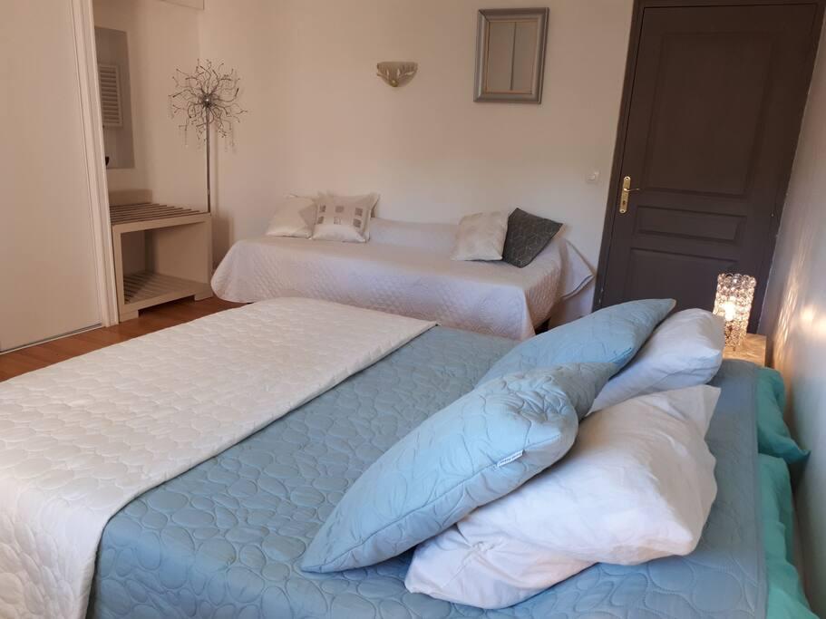 La grande chambre de 20m2 se compose d'un lit pour deux personnes ainsi que d'un  lit simple