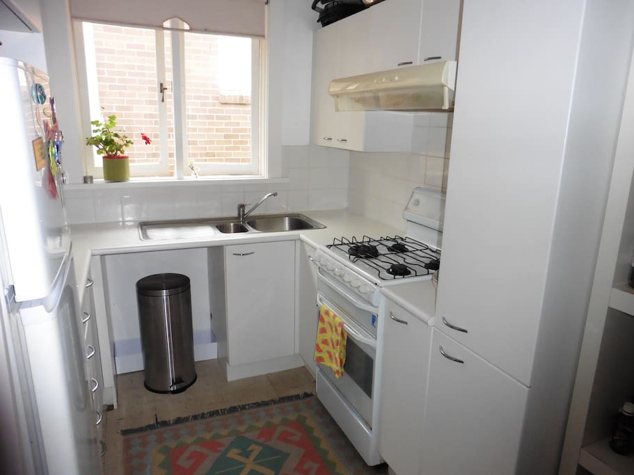 Fully equipped kitchen which includes a gas oven, microwave, blender, kettle, toaster, pod coffee machine and cookware.
