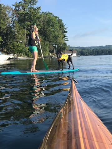 Lake Sunapee in the summer.  The view off the bow of a kayak with a guest and her dog.
