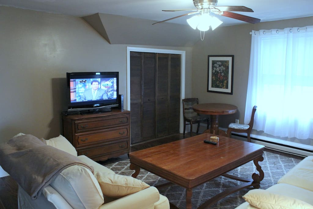 Large living room with comfortable couches, flat screen tv and cafe table