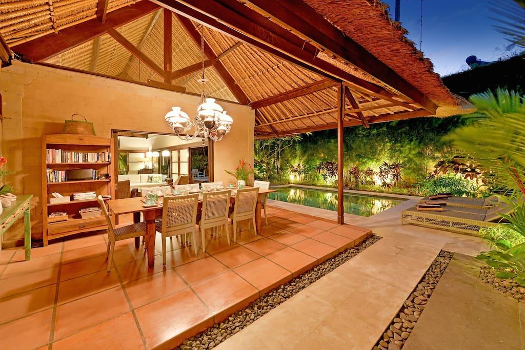 Poolside dining under soaring intricate bamboo roof