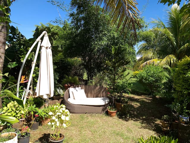 Lovely flat in a green tropical garden with pool.