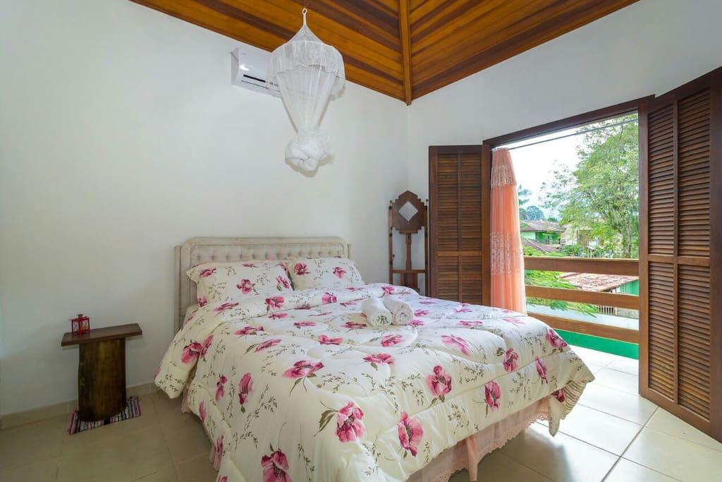 Suíte com cama queen e bela vista para as montanhas e o pôr do sol.