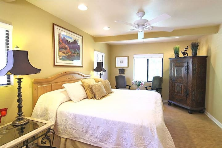 Master bedroom features a king sized bed, luxury linens and bamboo flooring
