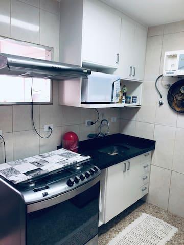 Cozinha: fogão, microondas, pia com água aquecida.