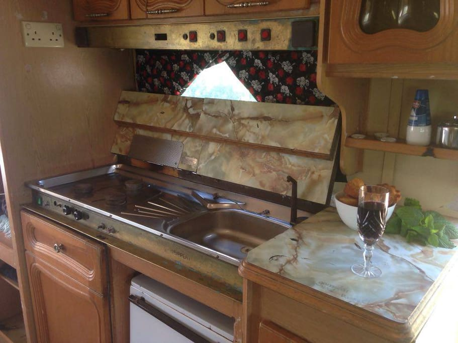 Kitchen area, equipped with fridge, a small oven and gas hob.