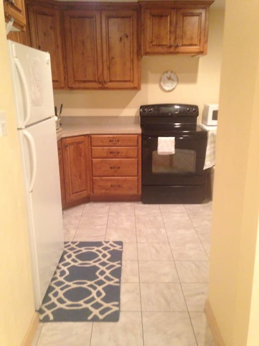 Kitchen with fridge, stove/oven and microwave.  Furnished dishes and cookware.